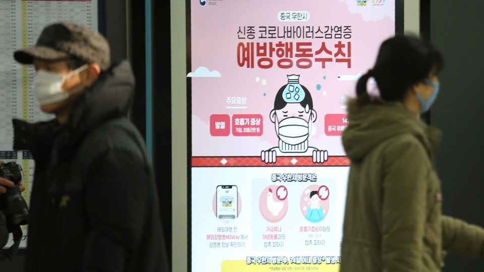"People pass by a poster warming about a new coronavirus at Suseo Station in Seoul, South Korea, Friday, Jan. 24, 2020. The sign reads ""Prevention."" (AP Photo/Ahn Young-joon)"