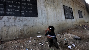 In this April 4, 2013 photo, before the start of class, an impoverished girl takes notes from a blackboard painted on a building wall at a free school run under a mass transit bridge in New Delhi, India. India's Right To Education Act promising free, compulsory schooling to all children ages 6 to 14 was supposed to take full effect March 31, 2013, but millions of children still don't go to school. (AP Photo/Altaf Qadri)