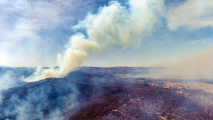 In this Jan. 24, 2020, photo provided by the New South Wales Police, smoke rises from an active wildfire near the crash site of a firefighting air tanker near Numeralla, south west of Sydney. (NSW Police via AP)