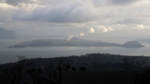FILE - Taal volcano spews steam as seen from Tagaytay, Cavite province, southern Philippines on Sunday Jan. 19, 2020. (AP Photo/Aaron Favila)