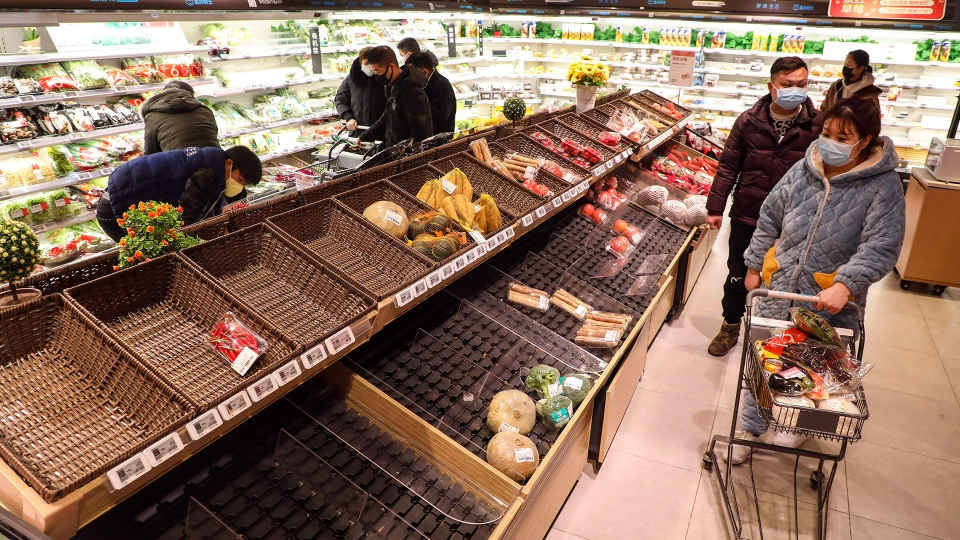 Shoppers wearing face masks look for groceries with many empty shelves at a supermarket in Wuhan in central China's Hubei province, Saturday, Jan. 25, 2020. The virus-hit Chinese city of Wuhan, already on lockdown, banned most vehicle use downtown and Hong Kong said it would close schools for two weeks as authorities scrambled Saturday to stop the spread of an illness that is known to have infected more than 1,200 people and killed 41, according to officials. (Chinatopix via AP)