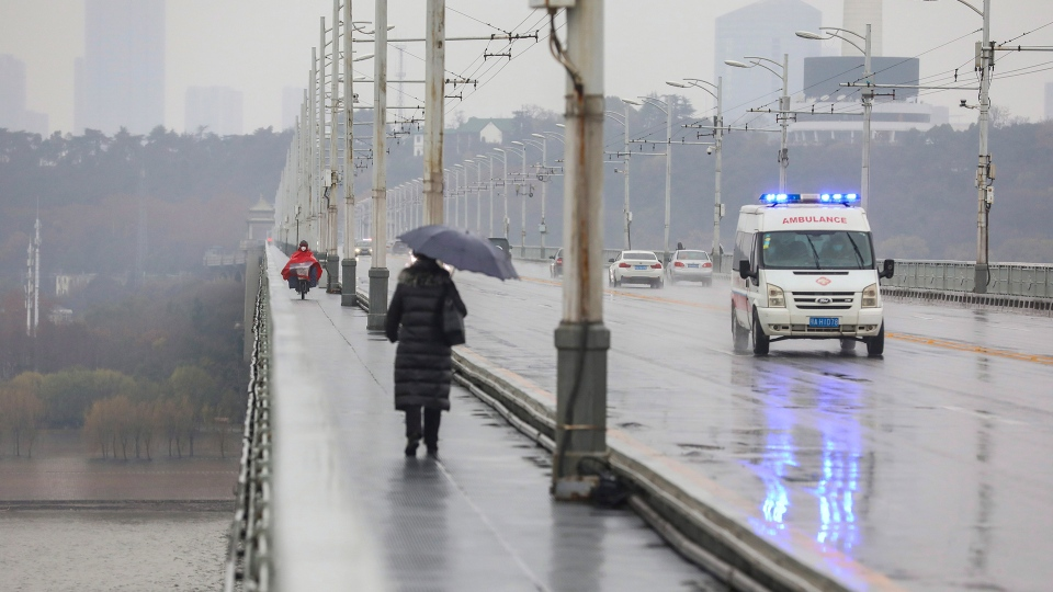 An ambulance drives across a bridge in Wuhan in central China's Hubei province, Saturday, Jan. 25, 2020. The virus-hit Chinese city of Wuhan, already on lockdown, banned most vehicle use downtown and Hong Kong said it would close schools for two weeks as authorities scrambled Saturday to stop the spread of an illness that is known to have infected more than 1,200 people and killed 41, according to officials. (Chinatopix via AP)