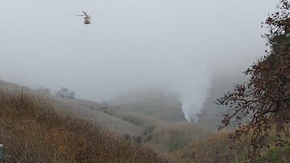 A police helicopter flies to the scene of a helicopter crash in Calabasas, Calif, where five people were killed on Jan. 26, 2020. (LA County Sheriff)
