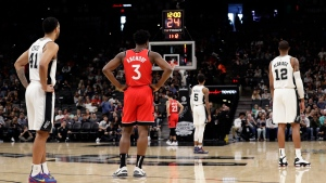 San Antonio Spurs players and Toronto Raptors players stop action during the first half of a basketball game to honor former NBA player Kobe Bryant, in San Antonio, Sunday, Jan. 26, 2020. Bryant died in a California helicopter crash Sunday. (AP Photo/Eric Gay)