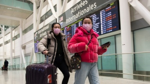 People wear masks as a precaution due to the coronavirus outbreak as they arrive at the International terminal at Toronto Pearson International Airport in Toronto on Saturday, January 25, 2020. Canadian health officials announced a first presumed case in Ontario after the illness has sickened more than 1,200 people and killed at least 41 in China, the epicentre of the outbreak. THE CANADIAN PRESS/Nathan Denette