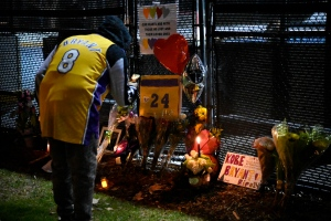 People gather outside of a basketball court where a small memorial was made in remembrance of former basketball player Kobe Bryant in Calabasas, Calif., Sunday, Jan. 26, 2020, following reports of his death in a helicopter crash in southern California. (AP Photo/Kelvin Kuo)