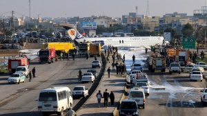 An Iranian passenger plane sits on a road outside Mahshahr airport after skidding off the runway, in southwestern city of Mahshahr, Iran, Monday, Jan. 27, 2020. An Iranian passenger airliner carrying some 150 passengers skidded off the runway and into a street next to the airport in the southern city of Mahshahr on Monday, after apparently losing its landing gear in a hard landing. (Mohammad Zarei/ISNA via AP)