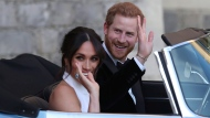 In this Saturday, May 19, 2018 file photo the newly married Duke and Duchess of Sussex, Meghan Markle and Prince Harry, leave Windsor Castle in a convertible car after their wedding in Windsor, England, to attend an evening reception at Frogmore House, hosted by the Prince of Wales. (Steve Parsons/pool photo via AP, File)