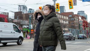 Pedestrians wear protective masks as they walk in Toronto on Monday, January 27, 2020. Canada's first presumptive case of the novel coronavirus has been officially confirmed, Ontario health officials said Monday as they announced the patient's wife has also contracted the illness. THE CANADIAN PRESS/Frank Gunn