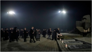 Poland's First Lady Agata Kornhauser-Duda, right, lays a candle by the International Monument at the Auschwitz-Birkenau Nazi death camp in Oswiecim, Poland, Monday, Jan. 27, 2020. Heads of State and survivors of the Auschwitz-Birkenau death camp gathered Monday for commemorations marking the 75th anniversary of the Soviet army's liberation of the camp, using the testimony of survivors to warn about the signs of rising anti-Semitism and hatred in the world today. (AP Photo/Markus Schreiber)