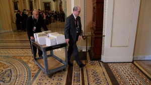 Documents are rolled through Capitol Hill, Monday, Jan. 27, 2020, in Washington, before the impeachment trial of President Donald Trump on charges of abuse of power and obstruction of Congress. (AP Photo/ Jacquelyn Martin)