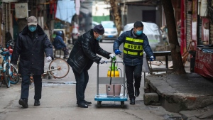 Government workers spray disinfectant along a street in Wuhan in central China's Hubei Province, Tuesday, Jan. 28, 2020. Hong Kong's leader announced Tuesday that all rail links to mainland China will be cut starting Friday as fears grow about the spread of a new virus. (Chinatopix via AP)