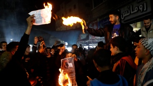 Protesters burn pictures showing U.S. President Donald Trump during a protest against the U.S. Mideast peace plan, at the main road market in Jebaliya refugee camp, Gaza Strip, Tuesday, Jan. 28, 2020. (AP Photo/Adel Hana)