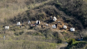 Investigators work Tuesday, Jan. 28, 2020 at the scene of a helicopter crash that killed former NBA basketball player Kobe Bryant, his 13-year-old daughter, Gianna, and seven others, in Calabasas, Calif. (AP Photo/Mark J. Terrill)