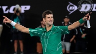 Serbia's Novak Djokovic celebrates after defeating Austria's Dominic Thiem in the men's singles final of the Australian Open tennis championship in Melbourne, Australia, Sunday, Feb. 2, 2020. (AP Photo/Lee Jin-man)