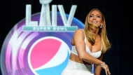 NFL Super Bowl 54 football game halftime performer Jennifer Lopez throws a football at a news conference Thursday, Jan. 30, 2020, in Miami. (AP Photo/David J. Phillip)