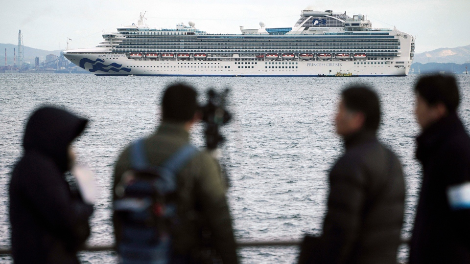 A TV crew film a cruise ship Diamond Princess anchoring off the Yokohama Port Tuesday, Feb. 4, 2020, in Yokohama, near Tokyo. Japanese health officials are conducting extensive medical checks on all 3,700 passengers and crew of the cruise ship that returned to the country after one passenger tested positive for the new coronavirus. (AP Photo/Eugene Hoshiko)