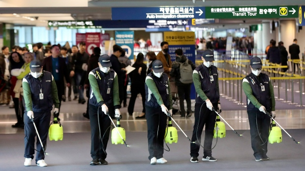 Workers spray antiseptic solution on the arrival lobby amid rising public concerns over the possible spread of a new coronavirus at Incheon International Airport in Incheon, South Korea, Tuesday, Jan. 21, 2020. Heightened precautions were being taken in China and elsewhere Tuesday as governments strove to control the outbreak of a novel coronavirus that threatens to grow during the Lunar New Year travel rush. (Suh Myung-geon/Yonhap via AP)