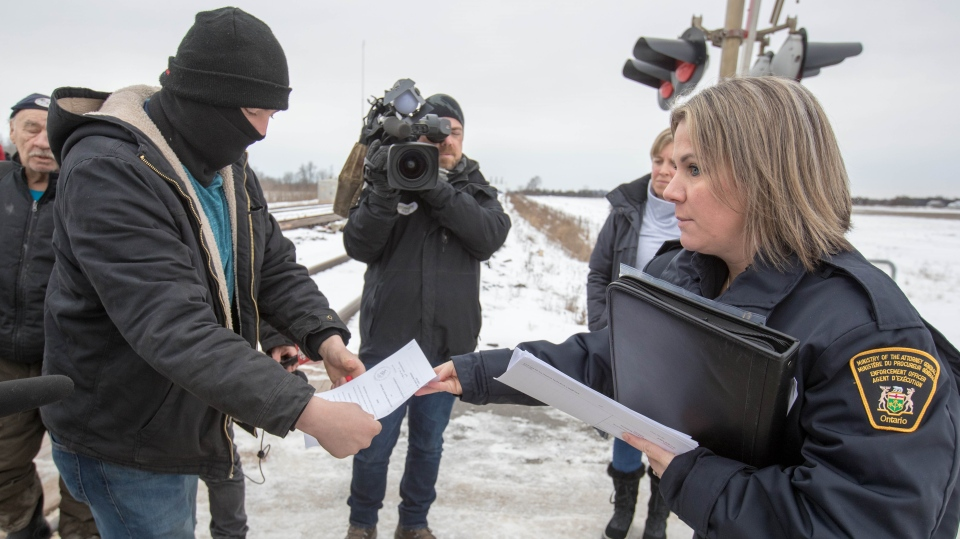 A court injunction is presented to members of the Mohawk Territory as they block the CN/VIA train tracks in Tyendinaga Mohawk Territory, near Belleville, Ont., on Tuesday, Feb. 11, 2020, in support of Wet'suwet'en's blockade of natural gas pipeline in northern B.C. THE CANADIAN PRESS/Lars Hagberg