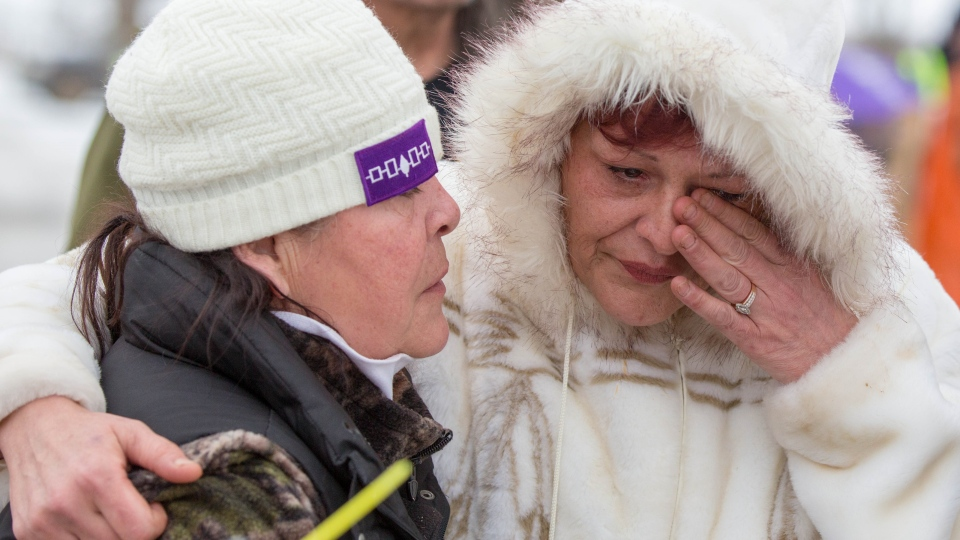 Two women from the Tyendinaga Mohawk Territory hug during the sixth day of blockade of the CN/VIA train tracks in Tyendinaga Mohawk Territory, near Belleville, Ont., on Tuesday, Feb. 11, 2020, in support of Wet'suwet'en's blockade of a natural gas pipeline in northern B.C. THE CANADIAN PRESS/Lars Hagberg