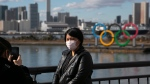 FILE - In this Jan. 29, 2020, file photo, a tourist wearing a mask poses for a photo with the Olympic rings in the background, at Tokyo's Odaiba district. (AP Photo/Jae C. Hong, File)
