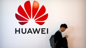 In this Oct. 31, 2019, file photo, a man uses his smartphone as he stands near a billboard for Chinese technology firm Huawei at the PT Expo in Beijing. The Justice Department has added new criminal charges against Chinese tech giant Huawei and two of its United States subsidiaries, accusing the company in a plot to steal trade secrets. The indictment from federal prosecutors was announced Thursday by federal prosecutors in Brooklyn. (AP Photo/Mark Schiefelbein, File)