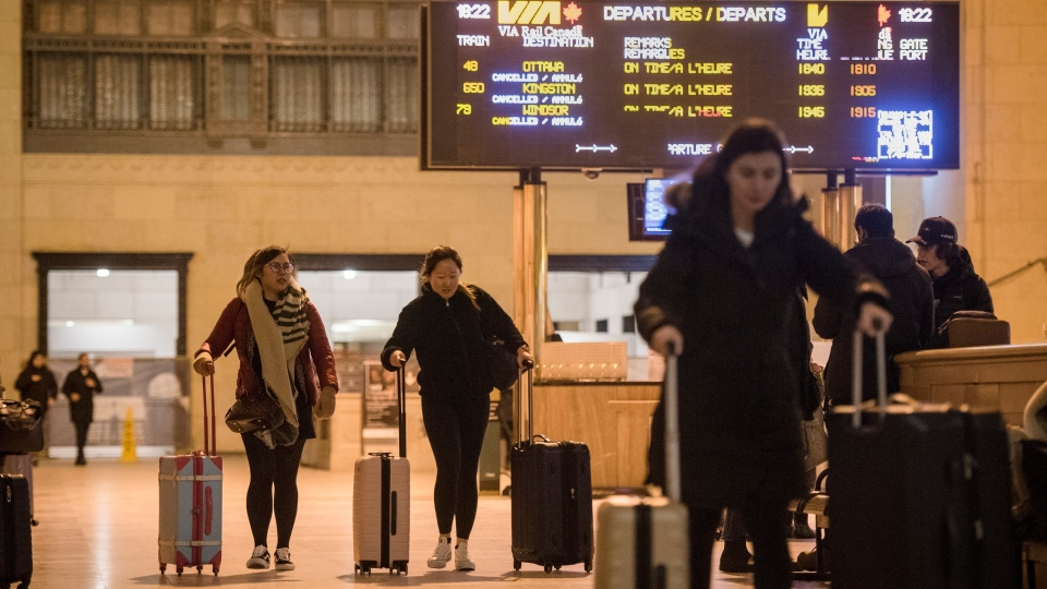 Travellers make their way through Union Station in Toronto as the departure display for Via Rail show all trains have been cancelled on Thursday, February 13, 2020. THE CANADIAN PRESS/ Tijana Martin