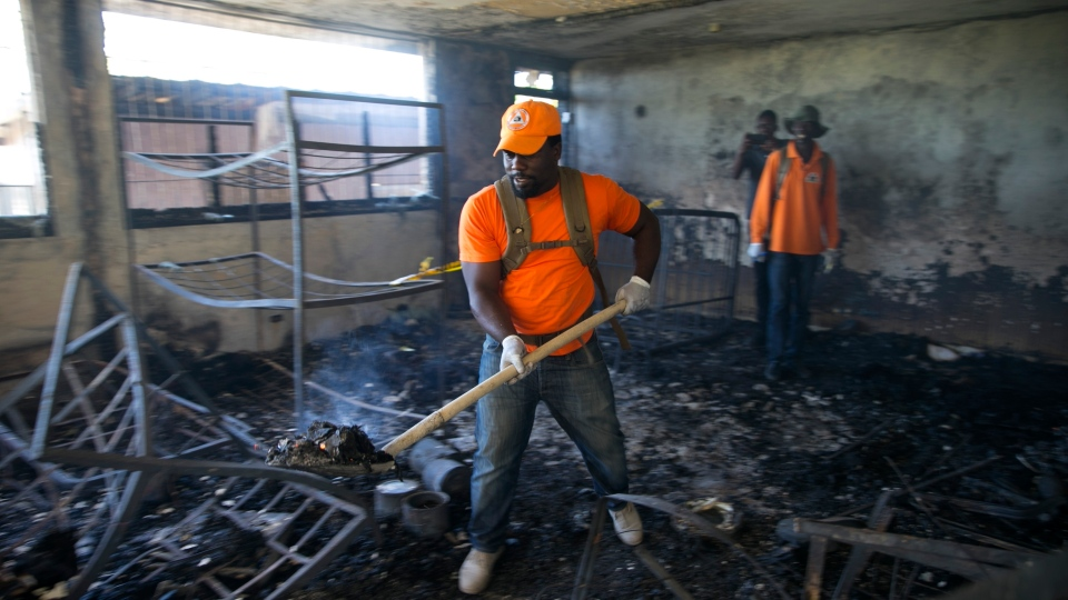 A civil protection worker shovels charred debris from inside the Orphanage of the Church of Bible Understanding where a fire broke out the previous night in Kenscoff, on the outskirts of Port-au-Prince, Haiti, Friday, Feb. 14, 2020. (AP Photo/Dieu Nalio Chery)