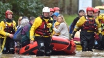"""Rescue operations continue as emergency services take residents to safety, in Nantgarw, Wales, Sunday Feb. 16, 2020. Storm Dennis is roaring across Britain with high winds and heavy rains, prompting authorities to issue 350 flood warnings, including a """"red warning"""" alert for life-threatening flooding in south Wales. (Ben Birchall/PA via AP)"""
