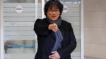 "South Korean director Bong Joon-ho gestures upon his arrival at the Incheon International Airport in Incheon, South Korea, Sunday, Feb. 16, 2020. South Koreans are reveling in writer-director Bong's dark comic thriller, ""Parasite,"" which won this year's Academy Awards for best film and best international feature. The movie itself, however, doesn't put the country in a particularly positive light. (AP Photo/Ahn Young-joon)"