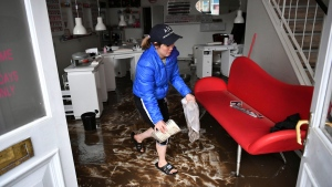 "An employee cleans a nail salon, after Storm Dennis hits the UK leading to widespread flooding, in Pontypridd, Wales, Sunday, Feb. 16, 2020. Storm Dennis roared across Britain with high winds and heavy rains Sunday, prompting authorities to issue some 350 flood warnings, including a ""red warning"" alert for life-threatening flooding in south Wales. (Ben Birchall/PA via AP)"