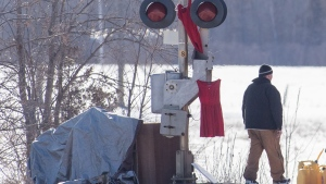 A protester walks past a train signal with red dresses during the twelfth day of protest in Tyendinaga, near Belleville, Ontario, on Monday Feb.17, 2020, as they protest in solidarity with the Wet'suwet'en hereditary chiefs opposed to the LNG pipeline in northern British Columbia. THE CANADIAN PRESS/Lars Hagberg