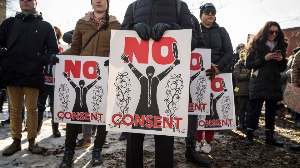 People hold signs at the start of a Family Day march in support of the Wet'suwet'en hereditary chiefs at Christie Pits Park in Toronto on Monday, February 17, 2020. THE CANADIAN PRESS/ Tijana Martin