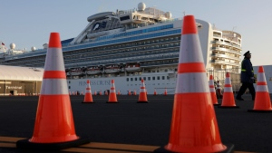 In this Feb. 13, 2020, file photo, a security guard stands near the quarantined Diamond Princess cruise ship in Yokohama, near Tokyo. (AP Photo/Jae C. Hong, File)