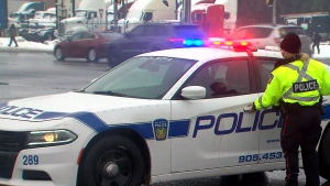 A Peel Regional Police officer is seen entering a cruiser at the scene of a Brampton crash on Tuesday morning. (CP24)