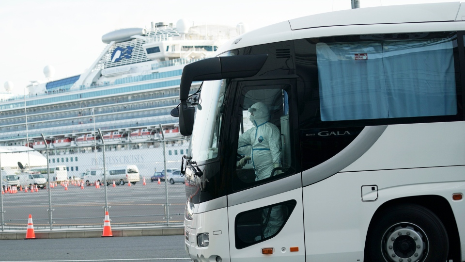 A bus carrying the passengers from the quarantined Diamond Princess cruise ship leaves a port in Yokohama, near Tokyo, Wednesday, Feb. 19, 2020. Hundreds of passengers began leaving the cruise ship Wednesday after the end of a much-criticized, two-week quarantine that failed to stop the spread of a new virus among passengers and crew. (AP Photo/Eugene Hoshiko)