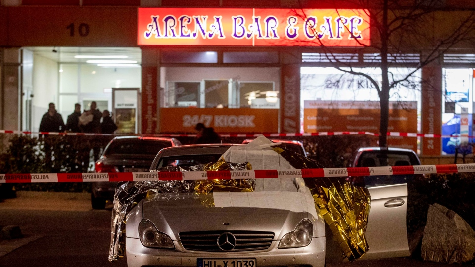 A car with dead bodies stands in front of a bar in Hanua, Germany Thursday, Feb. 20, 2020. German police say several people were shot to death in the city of Hanau on Wednesday evening. (AP Photo/Michael Probst)
