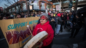 A woman beats a drum as protesters block an intersection in support of Wet'suwet'en Nation hereditary chiefs attempting to halt construction of a natural gas pipeline on their traditional territories, in Vancouver, on Wednesday, February 19, 2020. THE CANADIAN PRESS/Darryl Dyck