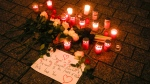 """Candles and flowers placed on the floor during a vigil for victims of last night's shooting in the central German town Hanau, at the Brandenburg Gate in Berlin, Germany, Thursday, Feb. 20, 2020. A 43-year-old German man who posted a manifesto calling for the """"complete extermination"""" of many """"races or cultures in our midst"""" shot and several people of foreign background on Wednesday night, most of them Turkish, in an attack on a hookah bar and other sites in a Frankfurt suburb, authorities said Thursday. (AP Photo/Markus Schreiber)"""