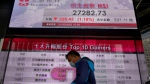 A man walks past a bank electronic board showing the Hong Kong share index at Hong Kong Stock Exchange Friday, Feb. 21, 2020. Asian stock markets have followed Wall Street lower after a rise in virus cases in South Korea refueled investor anxiety about China's disease outbreak.(AP Photo/Vincent Yu)