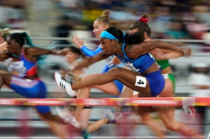 In this Oct. 5, 2019, file photo, Kendra Harrison, (4) of the United States, competes in a heat of the women's 100 meter hurdles at the World Athletics Championships in Doha, Qatar. The photo was part of a series of images by photographer David J. Phillip which won the Thomas V. diLustro best portfolio award for 2019 given out by the Associated Press Sports Editors during their annual winter meeting in St. Petersburg, Fla. (AP Photo/David J. Phillip, File)