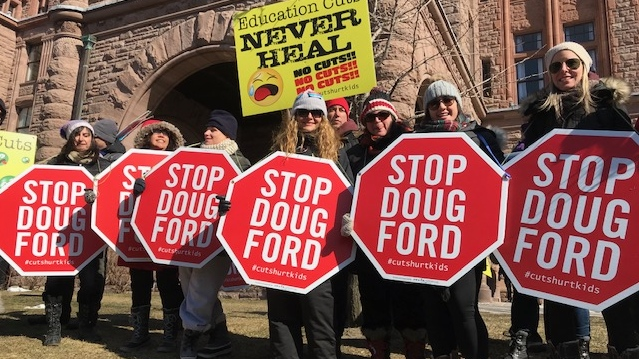 Teachers protesting at Queen's Park Friday February 21, 2020 hold placards and signs. (Cristina Tenaglia /CP24)