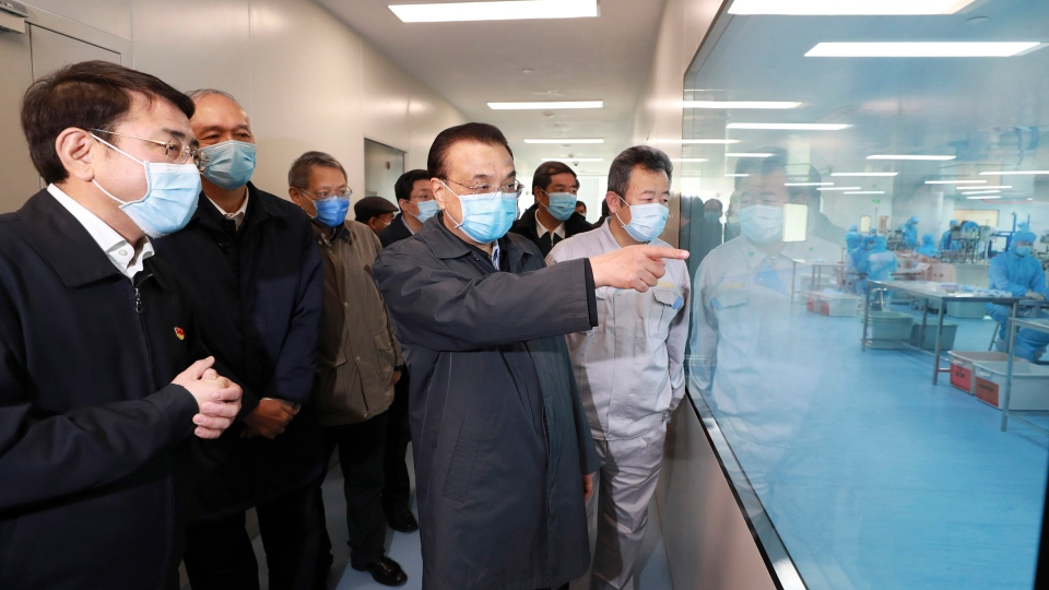 In this Friday, Feb. 21, 2020, photo released by China's Xinhua News Agency, Chinese Premier Li Keqiang, second from right, visits a mask production line at a medical supply company in Beijing. China's leadership sounded a cautious note Friday about the country's progress in halting the spread of the new virus, after several days of upbeat messages. (Ding Lin/Xinhua via AP)