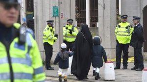 People arrive for midday prayers as police stand outside the London Central Mosque, near Regent's Park, north London, Friday Feb. 21, 2020, where a man was arrested on suspicion of attempted murder after an official at one of London's biggest mosques was stabbed during afternoon prayers on Thursday, police and mosque authorities said. (Kirsty O'Connor/PA via AP)