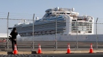 A photographer takes photos near the quarantined Diamond Princess cruise ship anchored at a port in Yokohama, near Tokyo, Friday, Feb. 21, 2020. Passengers tested negative for COVID-19 started disembarking since Wednesday. (AP Photo/Eugene Hoshiko)