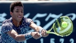 Canada's Felix Auger-Aliassime makes a backhand return to Latvia's Ernests Gulbis during their first round singles match at the Australian Open tennis championship in Melbourne, Australia, Tuesday, Jan. 21, 2020. (AP Photo/Dita Alangkara)