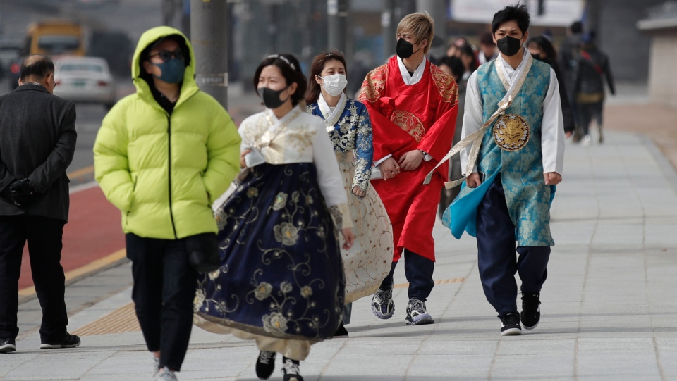 Visitors wearing face masks walk near the Gwanghwamun, the main gate of the 14th-century Gyeongbok Palace, and one of South Korea's well-known landmarks, in Seoul, South Korea, Saturday, Feb. 22, 2020. (AP Photo/Lee Jin-man)
