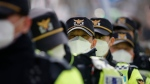 Police officers wearing face masks stand guard during a rally in downtown Seoul, South Korea, Saturday, Feb. 22, 2020. (AP Photo/Lee Jin-man)