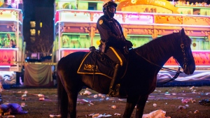A police officer works the scene where a man was reportedly hit and killed by a float of the Krewe of Endymion parade in the runup to Mardi Gras in New Orleans, Saturday, Feb. 22, 2020. A person was struck by a float and fatally injured Saturday evening during one of the iconic parades of the Mardi Gras season in New Orleans, authorities said. (Max Becherer/The Advocate via AP)