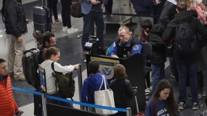 A TSA worker works at O'Hare airport in Chicago, Wednesday, Nov. 27, 2019. According to the source, the number of people traveling over the Thanksgiving holiday period is forecast to amount to 55.3 million in 2019. (AP Photo/Nam Y. Huh)